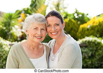 mãe, com, dela, filha, olhando câmera, jardim