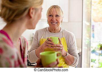 mãe filha, falando, café bebendo, em, cozinha