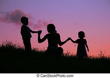 mãe, segura, crianças, para, a, mãos, a, pôr do sol