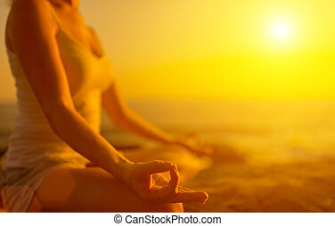 mão, de, mulher meditando, em, um, ioga posa, ligado, praia, em, pôr do sol