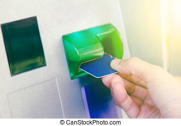 mão, inserindo, cartão atm, em, aterre máquina, retirar, dinheiro, de, mulher, com, cartão crédito, usando, um, atm, fundo, fundo, e, seletivo, foco.