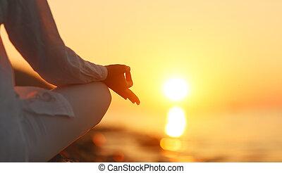 mãos, de, mulher meditando, em, ioga posa, em, pôr-do-sol praia