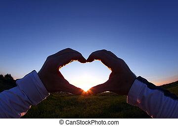 mãos fechadas, em, forma coração, ligado, um, fundo, pôr do sol