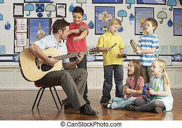 männlicher lehrer, spielende gitarre, mit, pupillen, haben, musik lektion, in, klassenzimmer
