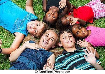 mångfaldig, grupp, og, barn, lagd, tillsammans, på, grass.