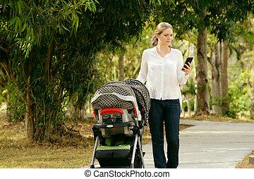 mère, à, bébé dans poussette, dactylographie, message, téléphone