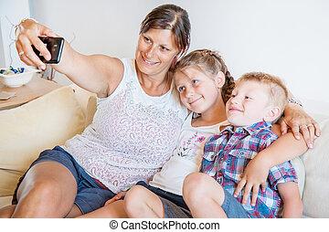 mère, famille heureuse, selfie, sofa., prendre, enfants, elle