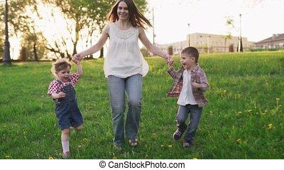 mère, parc, ensemble, courant, tenant mains, sourire, enfants, heureux