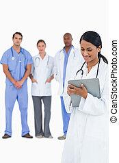 médico feminino, notas levando, com, staff membros, atrás de, dela