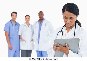 médico feminino, notas levando, ligado, área de transferência, com, staff membros, atrás de, dela, contra, um, fundo branco