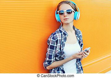 m�dchen, in, kopfhörer, hört, zu, musik, gebrauchend, smartphone, aus, bunte, hintergrund
