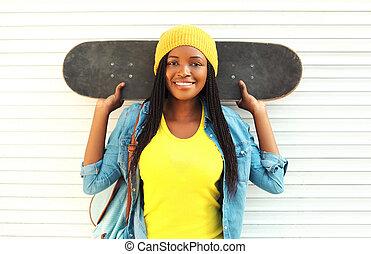 mód, meglehetősen, fiatal, mosolygós, african woman, noha, gördeszka, alatt, színes, öltözék, felett, white háttér