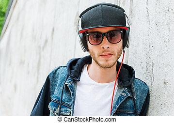 música, é, meu, life., sério, homem jovem, em, fones, olhando câmera, enquanto, inclinar-se, em, a, parede concreta