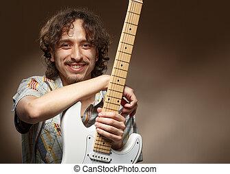 músico jovem, posar, em, estúdio, com, um, guitar.