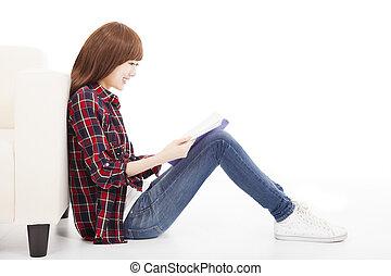 młoda kobieta, czytanie książka, i, posiedzenie na podłodze