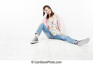 młoda kobieta, nastolatek, w, dżinsy, posiedzenie, na białym, podłoga