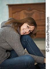 młoda kobieta, posiedzenie na podłodze