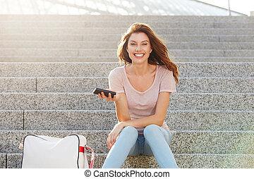 młoda kobieta, posiedzenie, outdoors, na, kroki, z, ruchoma głoska