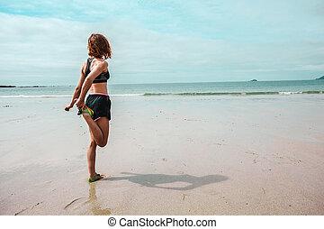 młoda kobieta, rozciąganie, jej, noga, na, plaża