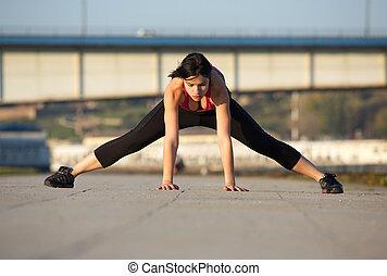 młoda kobieta, rozciąganie noga, mięśnie, z, ręki na podłodze