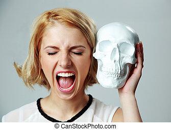 młoda kobieta, rozkrzyczany, i, dzierżawa, czaszka, na, szare tło
