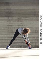 młoda kobieta, schylając, rozciąganie noga, mięśnie