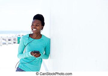 młoda kobieta, uśmiechanie się, z, ruchoma głoska, i, earphones