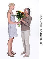 młoda kobieta, udzielanie, na, starszy, dama, kwiaty
