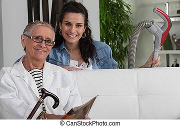 młoda kobieta, vacuuming, dla, na, starszy, dama