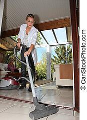 młoda kobieta, vacuuming