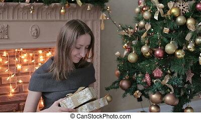 młoda kobieta, z, dary, przed, choinka