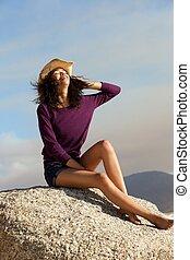 młoda kobieta, z, kapelusz, posiedzenie, na, skała, outdoors