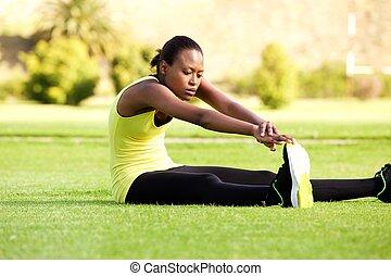 młody, afrykańska kobieta, posiedzenie na trawie, rozciąganie, do, osiągać, palce u nogi