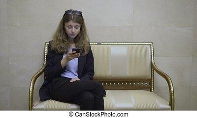 młody, kobieta interesu, w, niejaki, westybul hotelu, przeglądnięcie, jej, smartphone, ekran