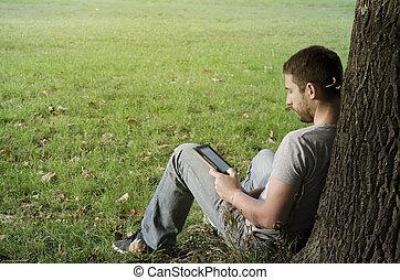 młody mężczyzna, czytanie, e-książka