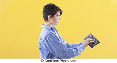młody mężczyzna, pisząc na maszynie, na, przedimek określony przed rzeczownikami, komputer