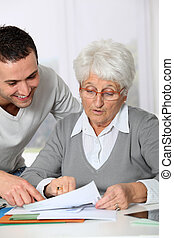 młody mężczyzna, porcja, starsza kobieta, z, paperwork