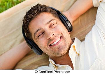 młody mężczyzna, słuchająca muzyka, w parku