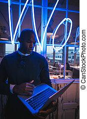 młody mężczyzna, w, biuro, pracujący dalejże, laptop