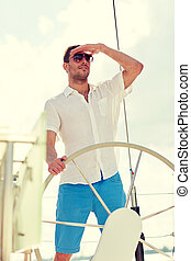 młody mężczyzna, w, sunglasses, kierownica, na, jacht