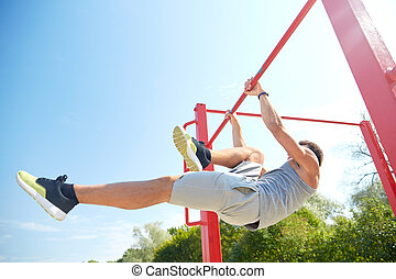 młody mężczyzna, wykonując, na, poziomy, bar, outdoors