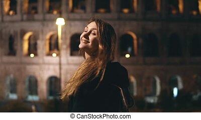 młody, piękna kobieta, reputacja, blisko, colosseum, w, rzym, włochy, spojrzenia, wstecz, w, aparat fotograficzny, i, uśmiechanie się, w, przedimek określony przed rzeczownikami, evening.