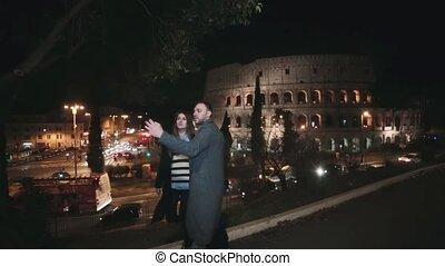 młody, piękny, para, reputacja, blisko, colosseum, w, rzym, włochy, i, mówiąc, selfie, fotografie, na, smartphone, w, przedimek określony przed rzeczownikami, wieczorny