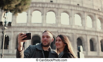 młody, pociągający, kobieta i obsadzają, reputacja, blisko, colosseum, w, rzym, italy., para, doprowadzenia, przedimek określony przed rzeczownikami, selfie, fotografia, na, smartphone.