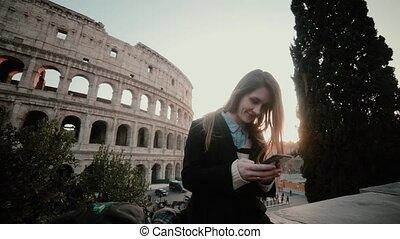 młody, pociągający, kobieta stanie, blisko, colosseum, w, rzym, włochy, i, używając, przedimek określony przed rzeczownikami, smartphone., uśmiechnięta dziewczyna, chatting.