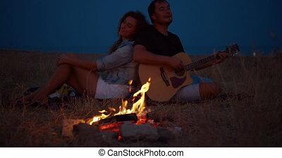 młody, posiedzenie, relationships., muzyka, interpretacja, szczęśliwy, guitar., para, człowiek, ognisko, romans, romantyk