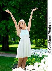 młody, uśmiechnięta kobieta, z, herb podniesiony, outdoors