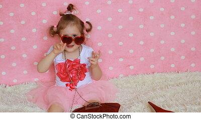 mała dziewczyna, hearts., fason, laughs., sunglasses, zabawny, sprytny, uśmiecha się, dziecko, fashionista., stroje, tło., czerwony, glamour., różowy, formułować