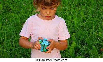 mała dziewczyna, rozwiązuje, rubik\'s, sześcian, na, zielona...