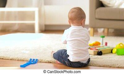 mały, chłopiec niemowlęcia, grając z zabawkami, w kraju